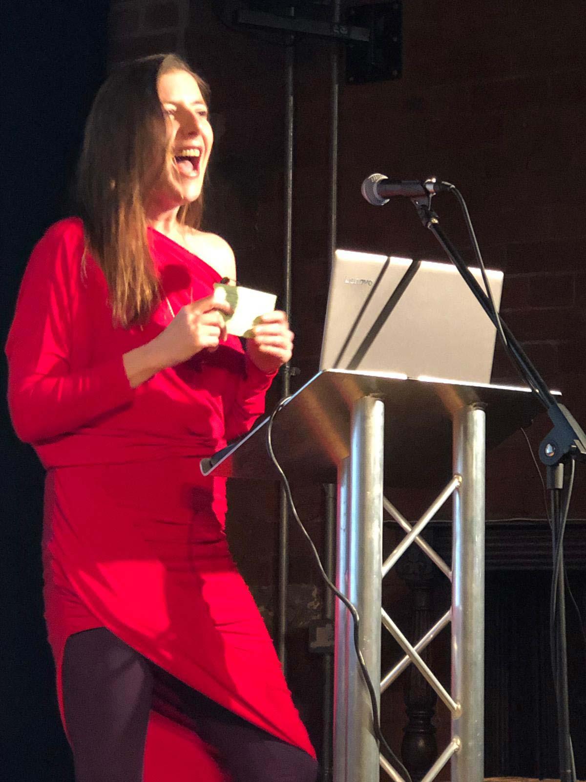 Sexologist, Sarah Rose Bright speaking in red dress
